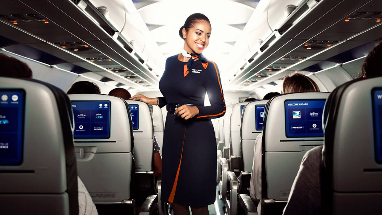 JetBlue crewmember stands in plane aisle smiling
