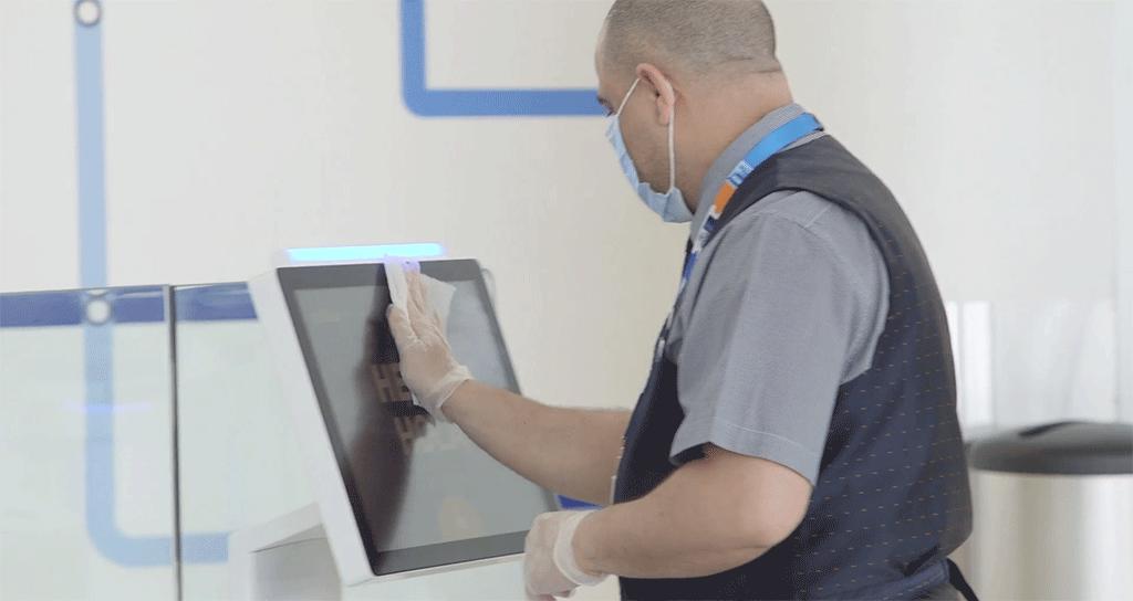 JetBlue crewmember wiping an airport kiosk