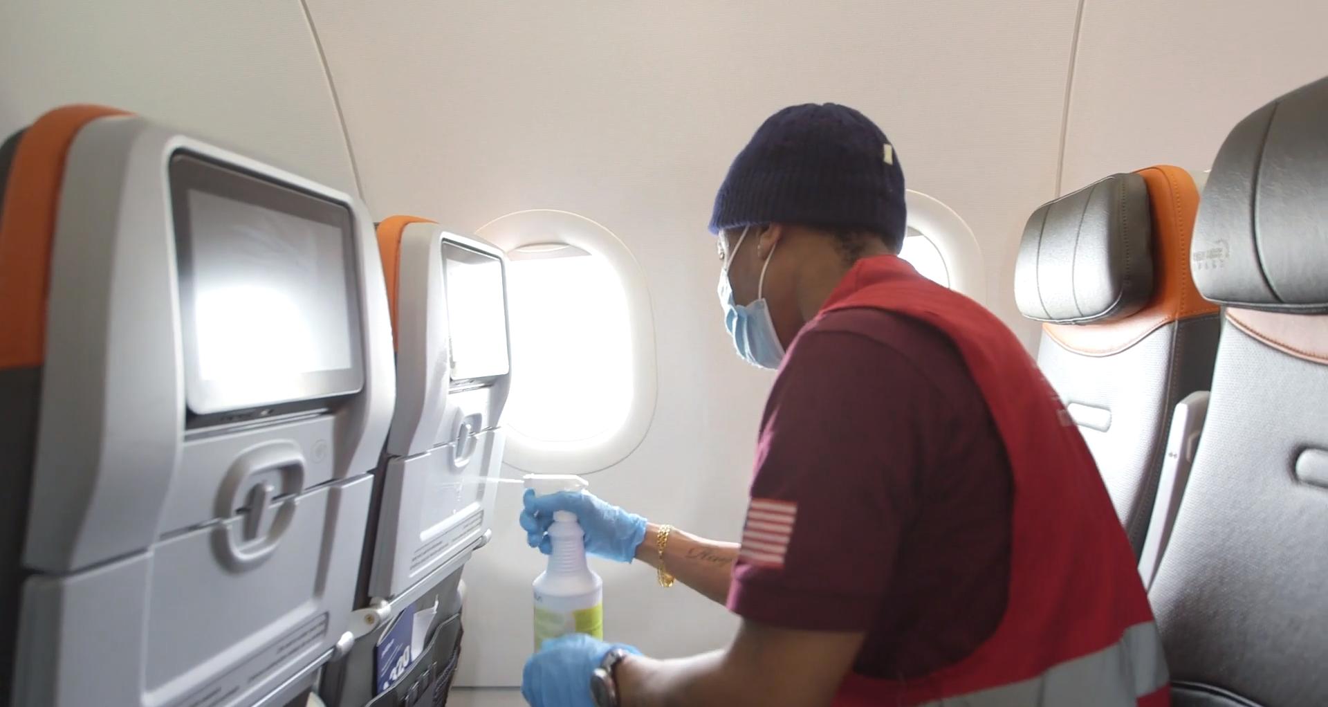 person spraying the digital seatback screen